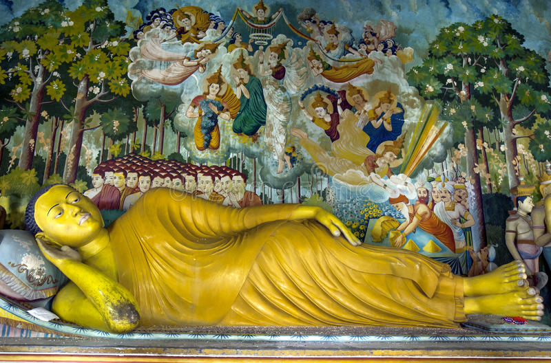 The Laying Buddha statue inside the Image House at Wewurukannala Vihara at Dickwella in Sri Lanka. The Laying Buddha statue with adjoining wall mural inside the stock image