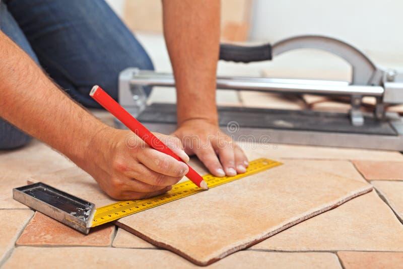 Laying ceramic floor tiles - man hands closeup. Laying ceramic floor tiles - man hands marking tile to be cut, closeup stock photo