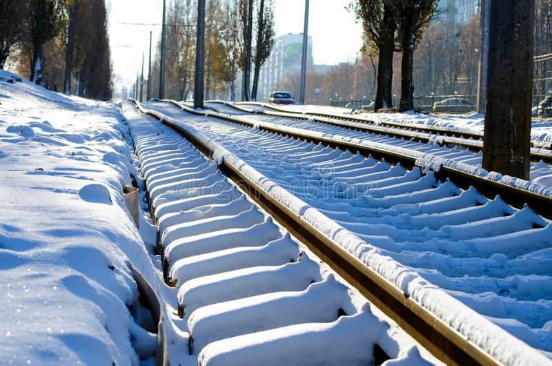 Laying the construction of new tram rails, snowy weather, rails and sleepers covered with snow royalty free stock photo