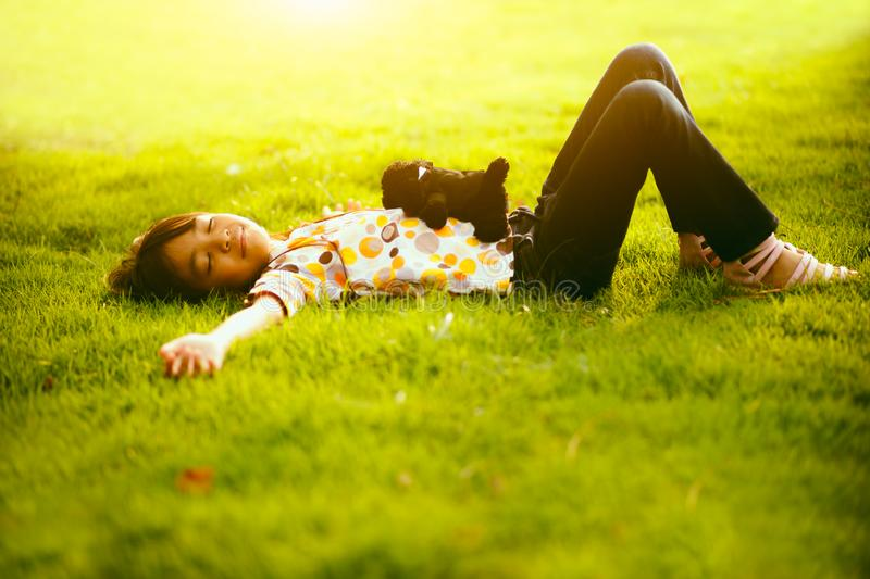Laying down. Little asian girl laying down on the green grass royalty free stock photography