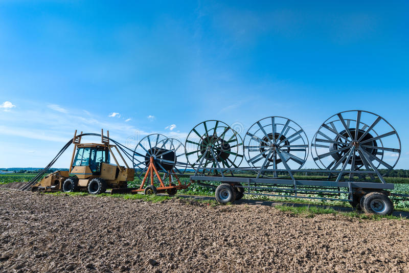 Laying of fiber optic cables. A tractor with trailers is laying fiber optic cables - glass fibers are employed as fiber optic cable for data transmission royalty free stock image