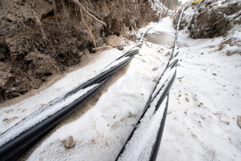 Laying a fiber optic and electricity cables in the frozen ground stock image