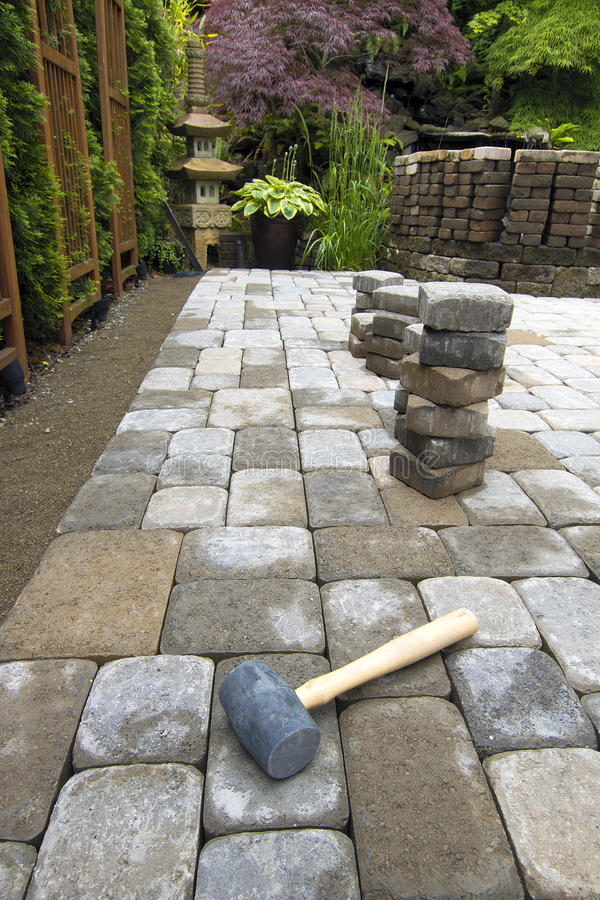 Laying Garden Pavers Patio. Laying Garden Cement Pavers Patio for Backyard Hardscape Landscaping royalty free stock image