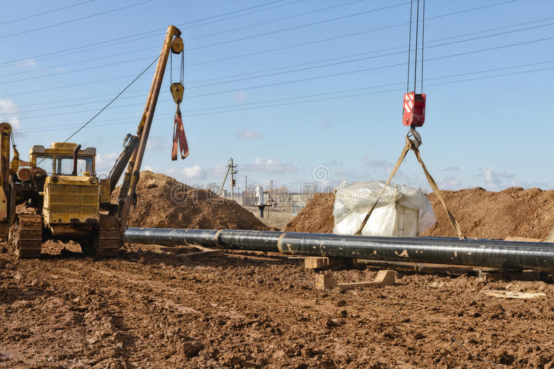 Laying of gas main in a trench dug in the field. Near the power line stock photography