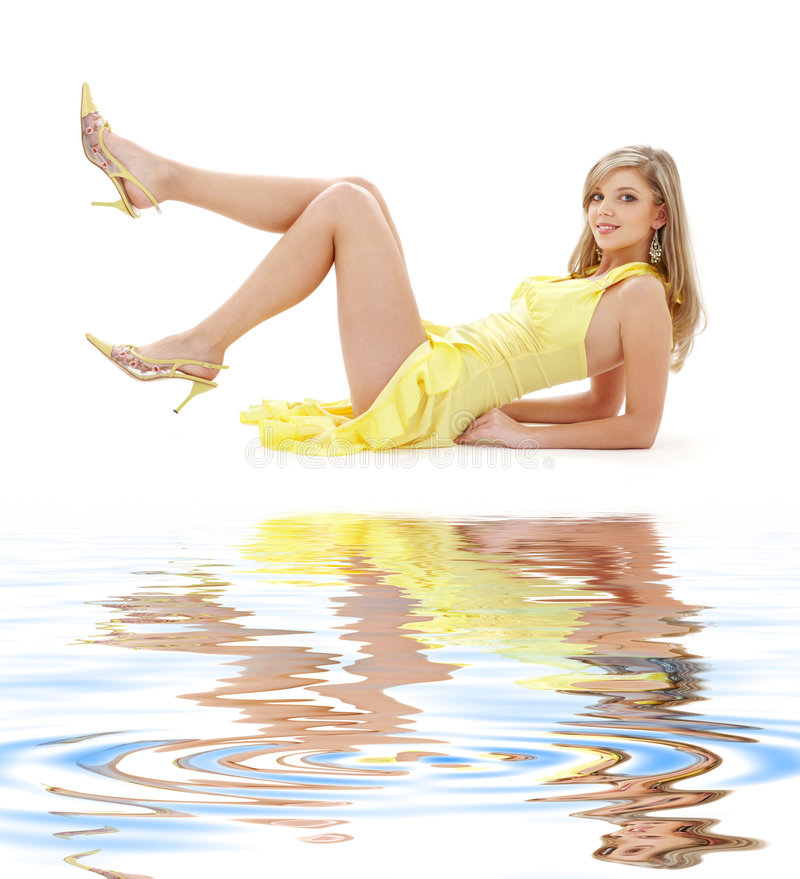 Laying girl in yellow dress on white sand stock image
