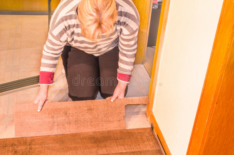 Laying laminate. Laying of floor covering. Here processing of vinyl laminate floor in the old building stock photo