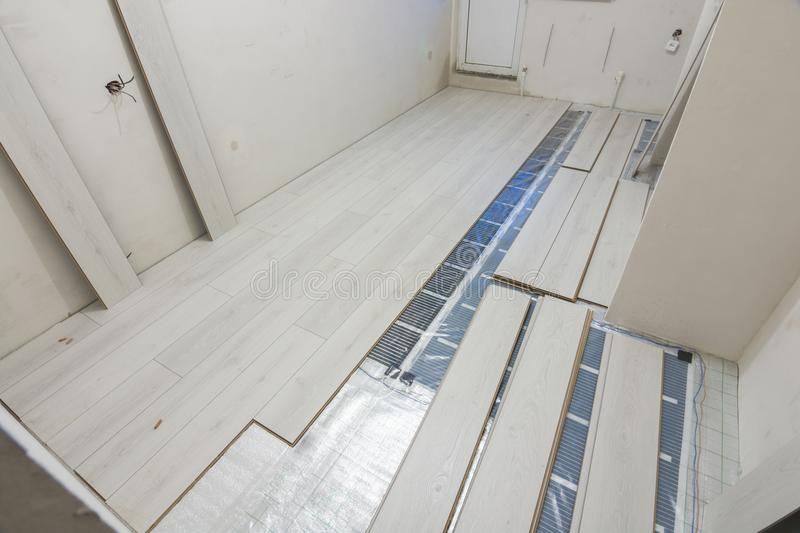 Laying laminate warm floor film. Laying laminate with warm floor film stock photography