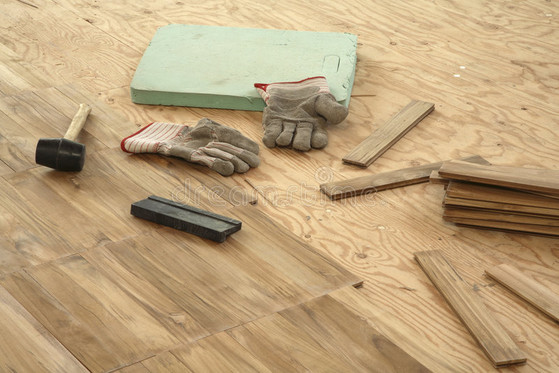 Laying parquet flooring. Newly laid parquet flooring stretches in a diagonal line from top left to bottom right across half the frame. Subfloor on right with a royalty free stock images