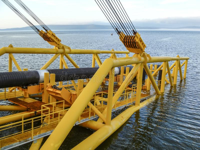 Laying of pipes with pipe-laying barge crane near the shore. Des royalty free stock image