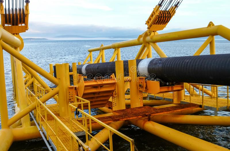 Laying of pipes with pipe-laying barge crane near the shore. Descent of the pipeline to a bottom exhausting with the pipelaying royalty free stock photos
