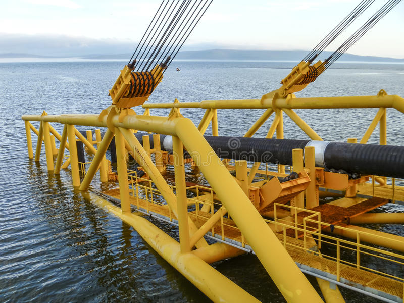 Laying of pipes with pipe-laying barge crane near the shore. Descent of the pipeline to a bottom exhausting with the pipelaying b royalty free stock image