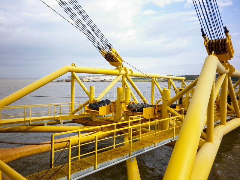Laying of pipes with pipe-laying barge crane near the shore. Descent of the pipeline to a bottom exhausting with the pipelaying ba royalty free stock photo