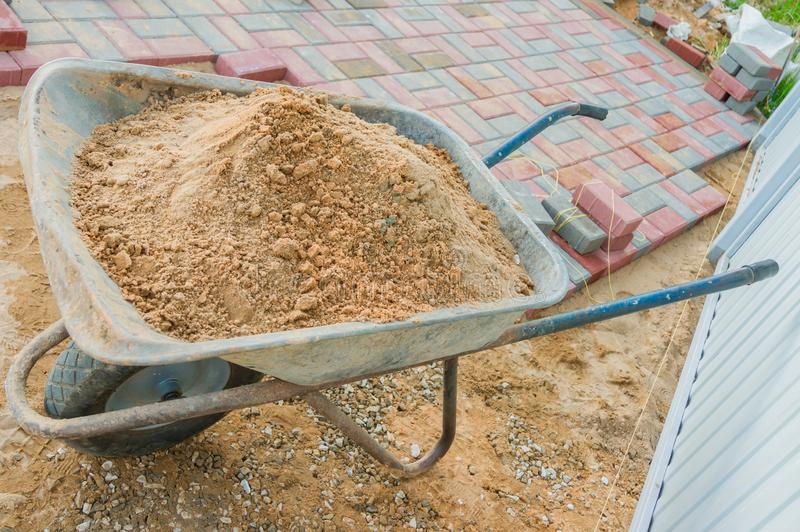 Laying red and gray concrete paving blocks. Road Paving, construction. Wheelbarrow full of sand.  royalty free stock photos
