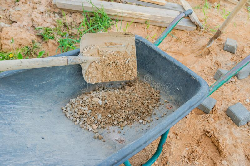 Laying red and gray concrete paving blocks. Road Paving, construction. Wheelbarrow full of sand. Road Paving, construction. Wheelbarrow full of sand royalty free stock photos