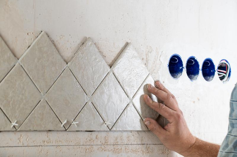 Laying tile, hand of the master stock images