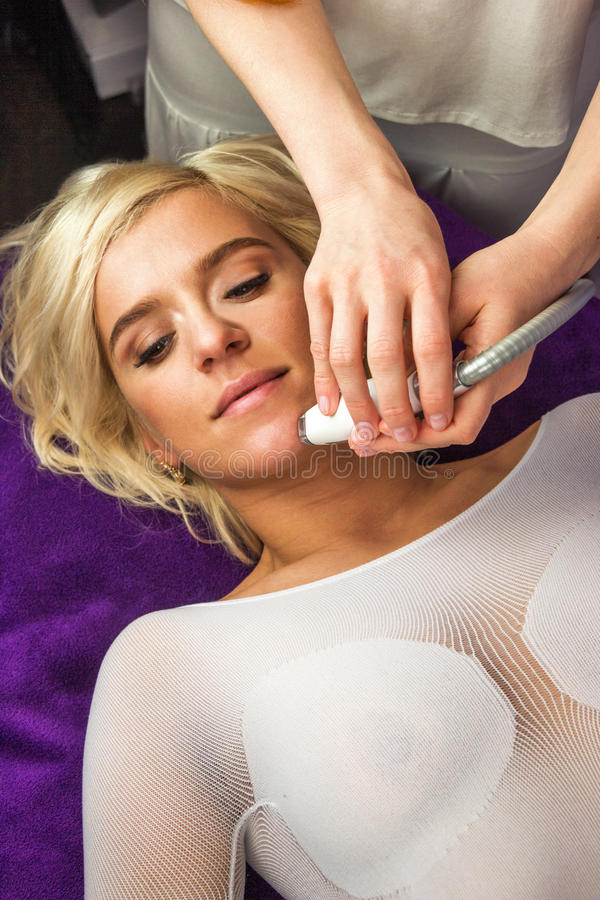 Laying woman getting laser and ultrasound facial therapy royalty free stock photo