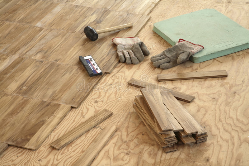 Laying wood flooring. Newly laid flooring stretches in a diagonal line across left half of frame . Subfloor on right with a pair of work gloves, a rubber royalty free stock image