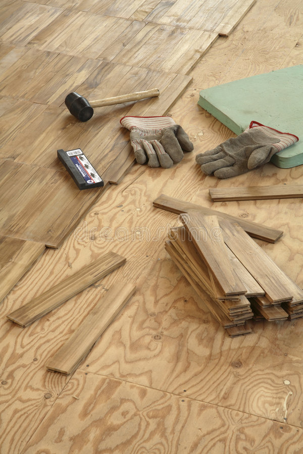 Laying wood flooring. Newly laid flooring stretches in a diagonal line across top third of frame Small sections of teak in parquet size. Subfloor on right with royalty free stock photos