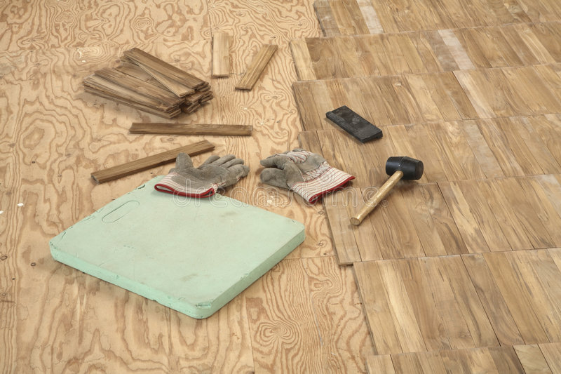 Laying wooden parquet flooring. Newly laid flooring on right half of frame. Subfloor on left with green kneeing mat in foreground with a pair of work gloves, a stock photo