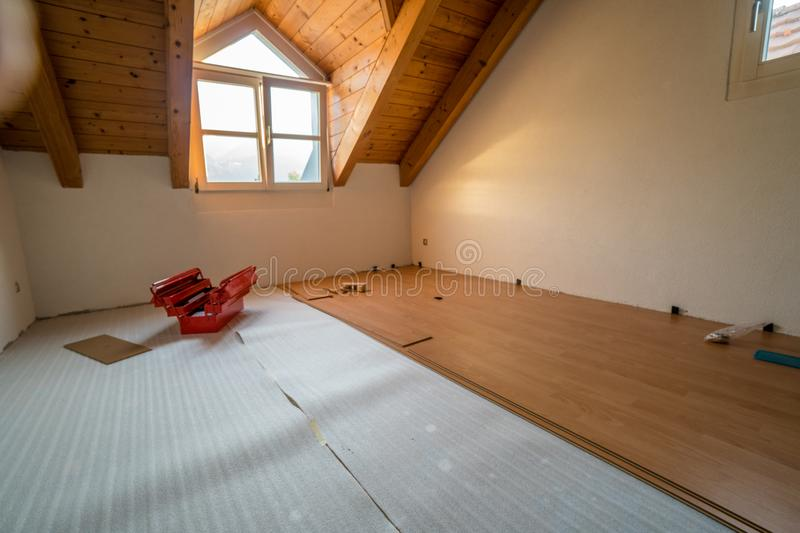 Laying wooden flooring during renovation work. Laying wooden parquet flooring during renovation work with a red toolbox in the background royalty free stock photos