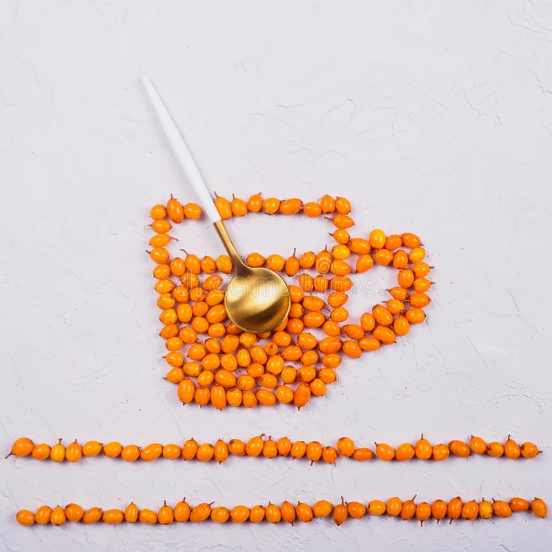 Creative layout of sea buckthorn berries on a neutral gray background. A layout of bright orange sea buckthorn berries in the shape of a cup of tea with spoon royalty free stock image