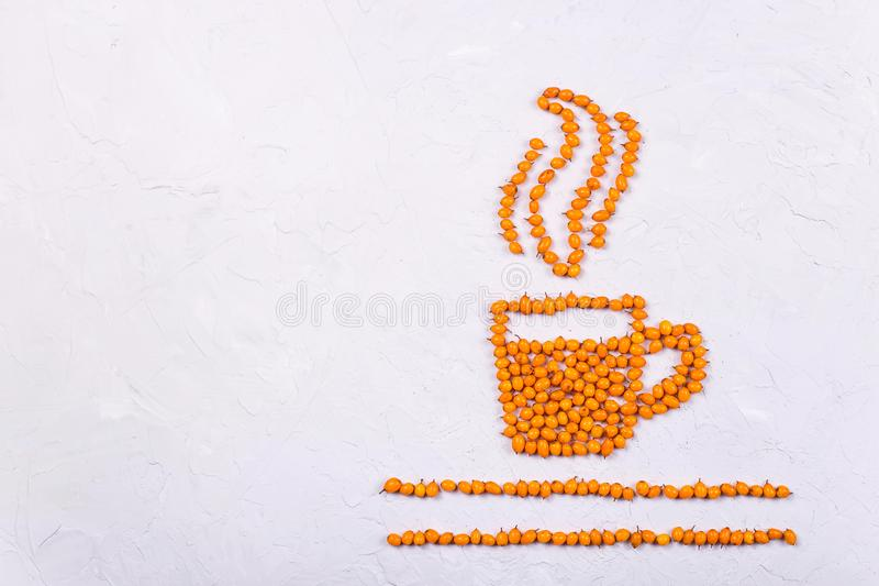 Creative layout of sea buckthorn berries on a neutral gray background. A layout of bright orange sea buckthorn berries in the shape of a cup of tea with steam royalty free stock photos