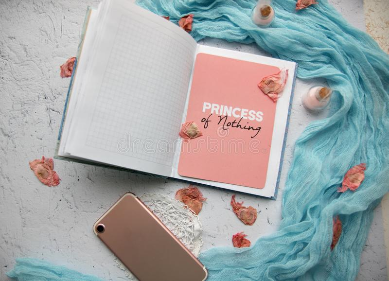 Blue and pink flatlay. Layout on a light marble background, a blue bluff, a ribbon and open notepad, pink card with the inscription `Princess of nothing` and royalty free stock photography