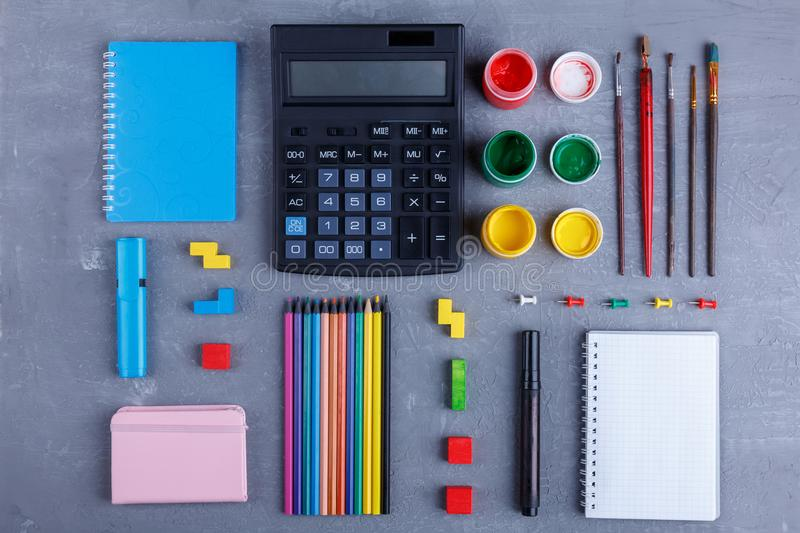 Layout of lots of different stationery . The concept of education. Top view. Layout of lots of different stationery of different colors. On a gray background stock images