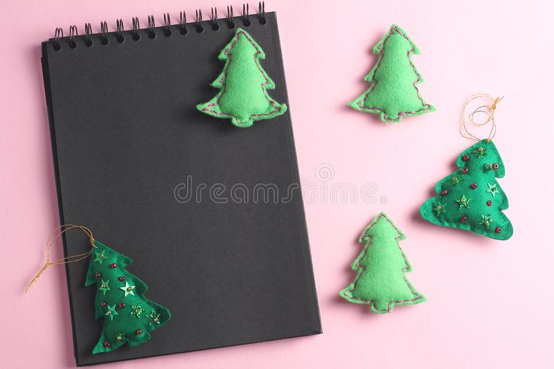 Layout for Merry Christmas to-do list. black notebook on pink background. toys made of felt in the form of green fir trees, flat. Lay, holiday concept royalty free stock photo