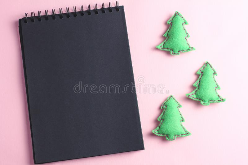 Layout for Merry Christmas to-do list. black notebook and toys made by hand from felt on a pink background. flat lay, copy space, royalty free stock images