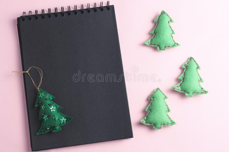 Layout for Merry Christmas to-do list. black notebook and toys made by hand from felt on a pink background. flat lay, copy space stock photography