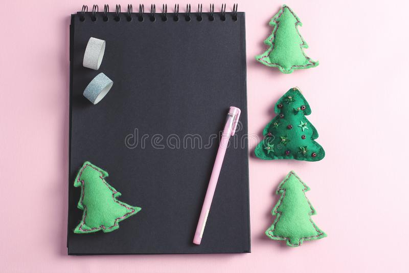 Layout for Merry Christmas to-do list. stationery - pen, notebook and decorative tape were photographed from above on a pink stock photography