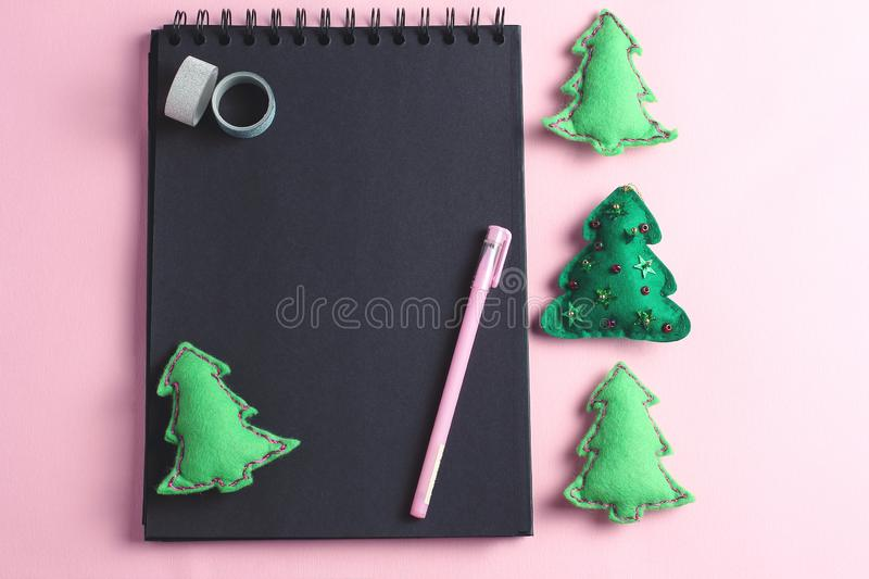 Layout for Merry Christmas to-do list. stationery - pen, notebook and decorative tape were photographed from above on a pink royalty free stock images