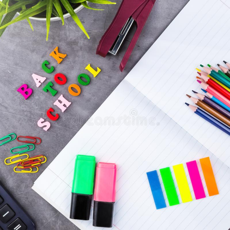 The layout of school supplies on a dark gray background. Top view, the sun`s rays from the side. Flat lay stock images