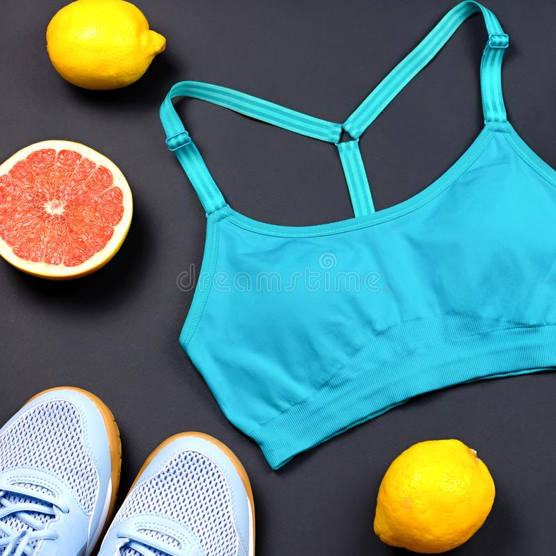 Layout of sport clothes and accessories for women with fruits on black background royalty free stock photos