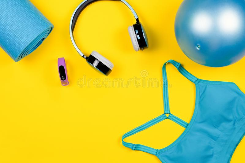Layout of sport clothes and accessories for women with fruits on yellow background royalty free stock image