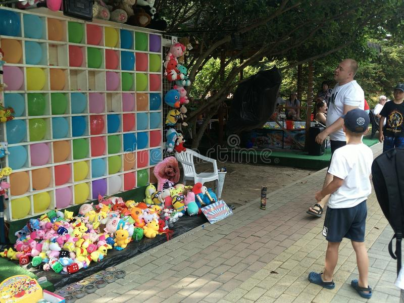 Lazarevskoye,俄罗斯6月20日2019年:一个十几岁的男孩瞄准在色的气球墙壁的一个目标  游乐场吸引力, 库存图片