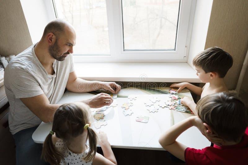 Lazer da família: pai, filhos e jogos de mesa do jogo da filha junto foto de stock