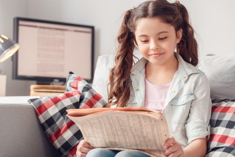 Lazer da menina em casa que senta o jornal da leitura concentrado imagem de stock royalty free