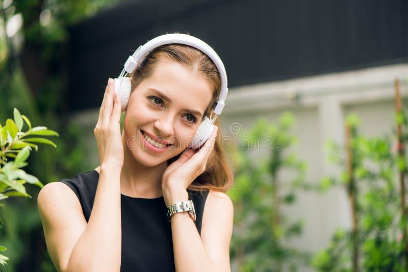Lazer dos povos e conceito da tecnologia - jovem mulher atrativa que escuta a música no jogador de música dentro fora imagens de stock