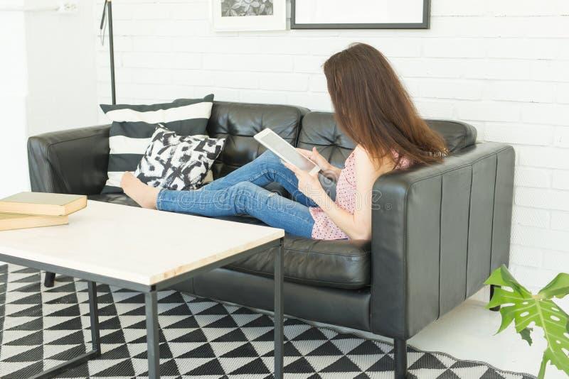 Lazer, tecnologia e conceito dos povos - mulher moreno nova que usa a tabuleta em casa imagens de stock