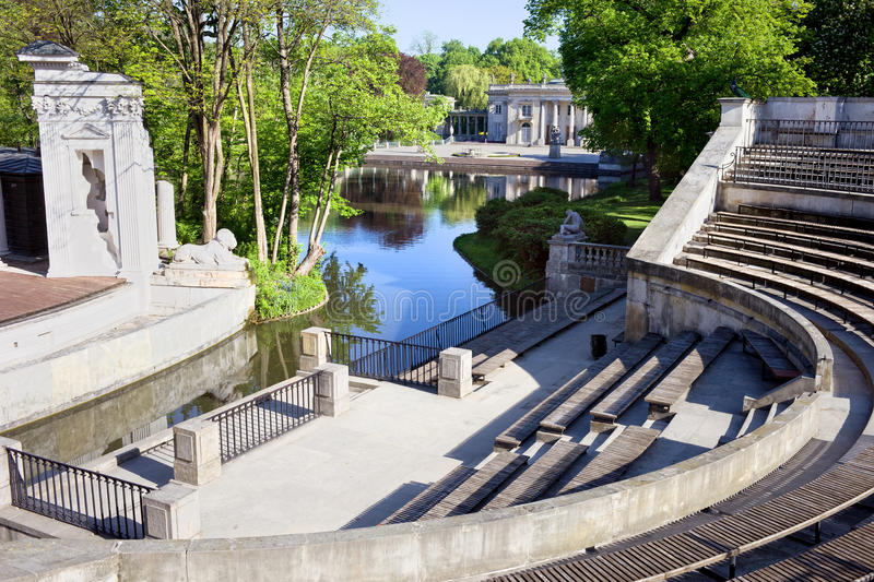 Lazienki Park in Warsaw. Lazienki Park (Royal Baths, Polish: Park Lazienkowski, Lazienki Krolewskie) with Roman inspired amphitheatre and Palace on the Water at stock photo