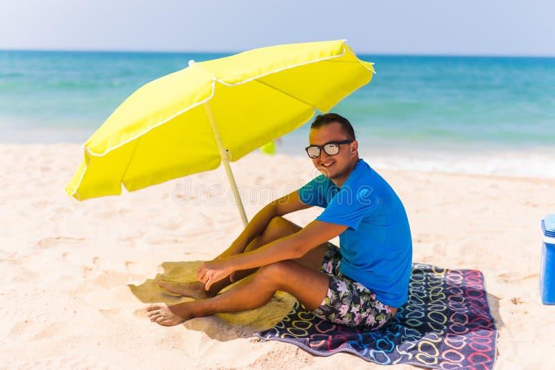Lazing человек в солнце под солнечным зонтиком на полотенце наслаждается ленивым временем на пляже стоковые изображения
