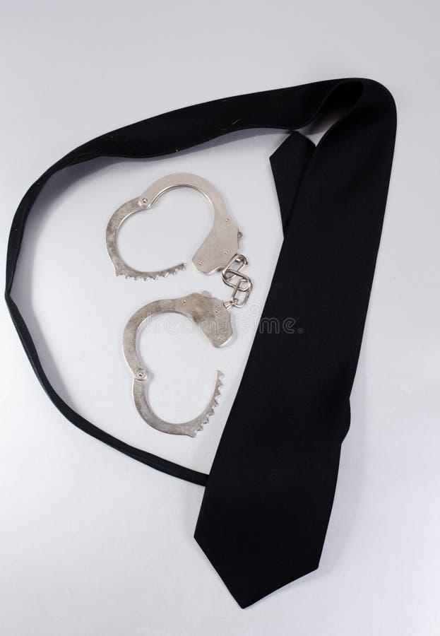 Lazo negro y esposas imagen de archivo libre de regalías