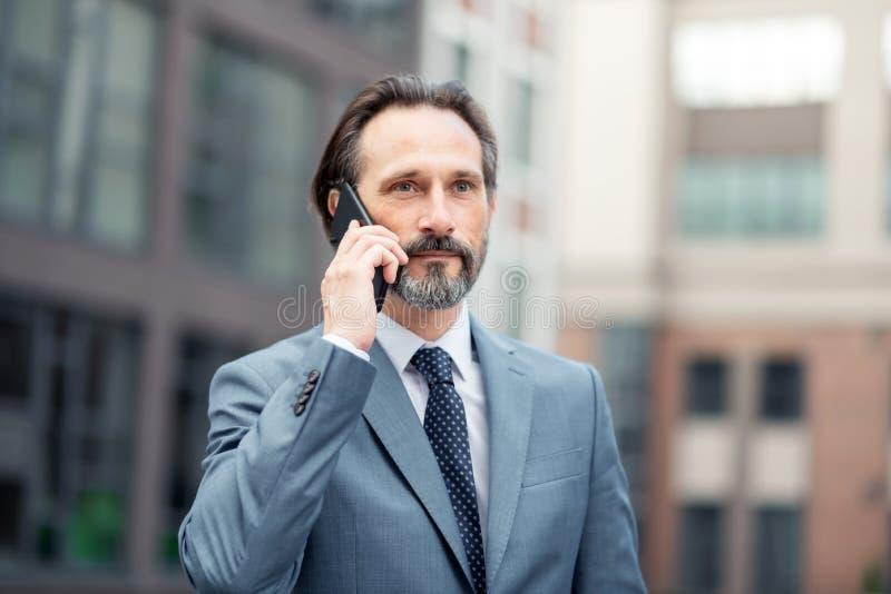 Lazo que lleva del hombre de negocios que llama a su socio comercial fotografía de archivo libre de regalías