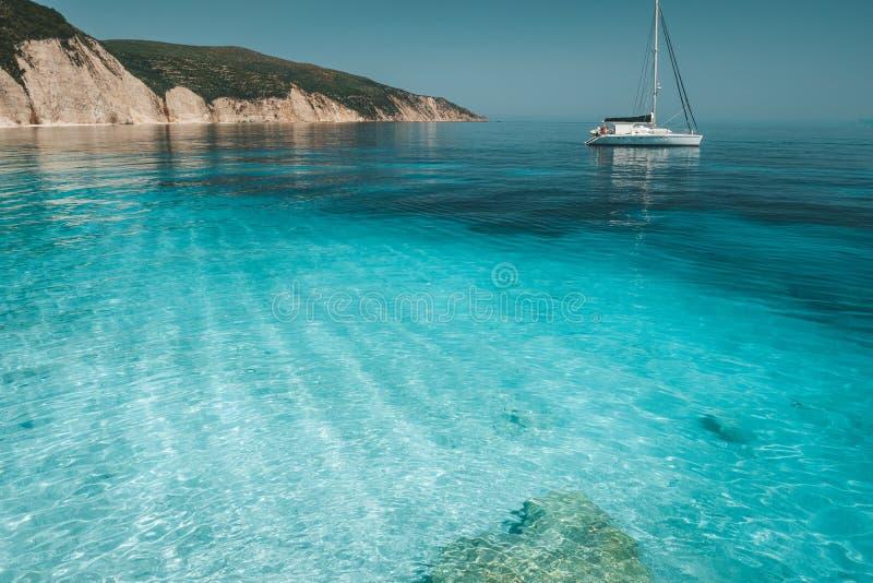 Lazurowa błękitna laguna z spokój fala i dryftową żeglowania catamaran jachtu łodzią Skalista falezy linia brzegowa w tle obrazy stock