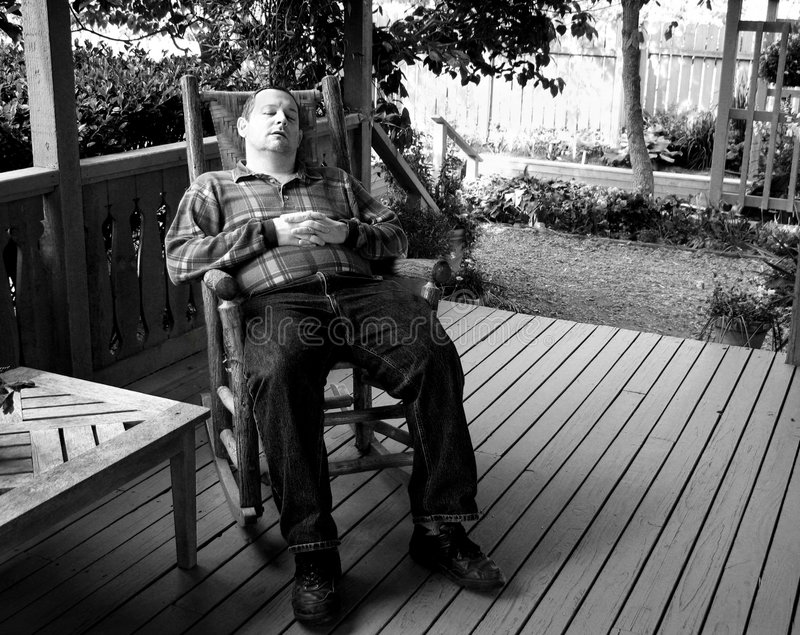 Lazy afternoon. Man napping in a rocking chair on front porch royalty free stock images