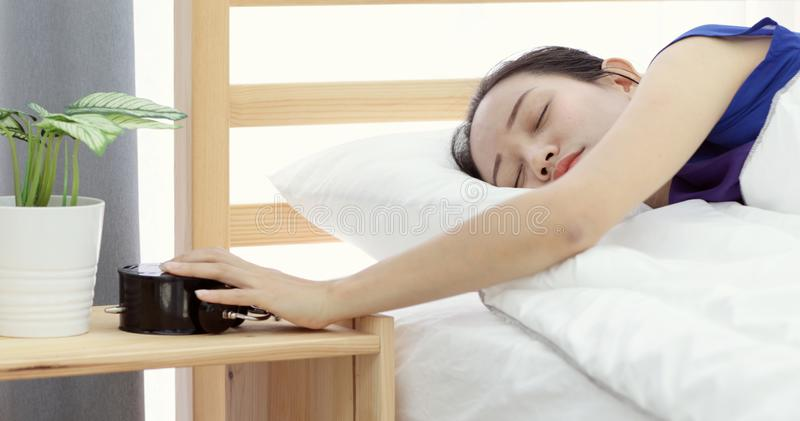 Lazy asian woman refusing to wake up lying on her bed stock images