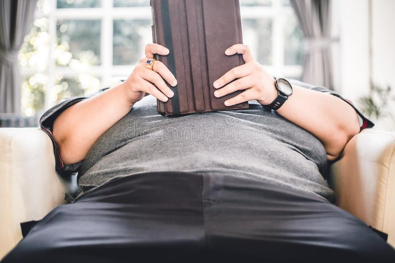 Lazy big fat man sitting at sofa play tablet all day no activity unhealthy lifestyle bad habit. Front view royalty free stock image