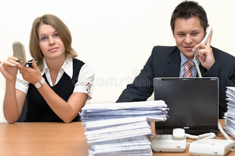 Lazy businesswoman and working businessman. The working businessman and the idling woman the secretary. On a white background. The office royalty free stock photo